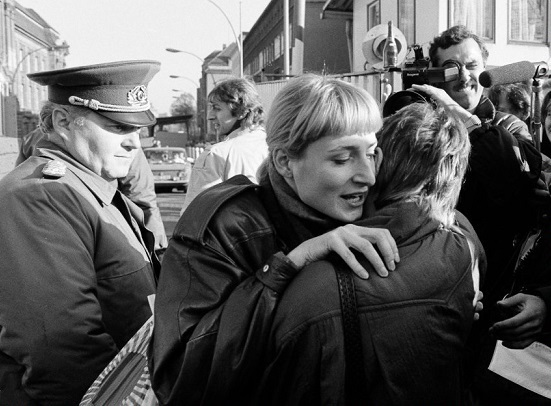 An East Berlin citizen embraces a West Berlin woman while an East German border soldier looks on in Berlin
